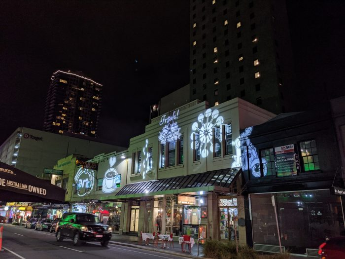 Gobos representing elements of the East End story illuminate buildings on Rundle Street